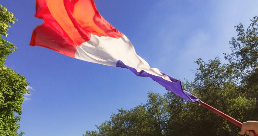 Drapeau français claquant au vent sur ciel bleu